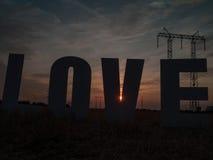 Lettres d'amour de photo sur le fond de coucher du soleil Photographie stock libre de droits