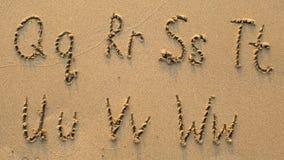 Lettres de l'alphabet écrit sur la plage sablonneuse Images stock