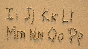 Lettres de l'alphabet écrit sur la plage sablonneuse Image libre de droits
