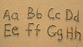 Lettres de l'alphabet écrit sur la plage sablonneuse Images libres de droits