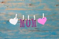 Lettres de MAMAN Message de jour de mères avec des coeurs accrochant avec des pinces à linge au-dessus du conseil en bois bleu Images stock
