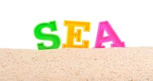 Lettres de mer sur un sable de plage sur un blanc Photos libres de droits