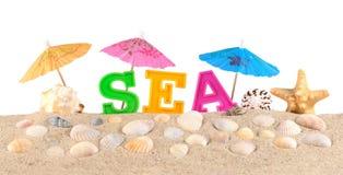 Lettres de mer sur un sable de plage sur un blanc Photo stock