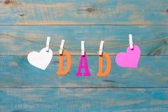 Lettres de PAPA Message de jour de pères avec des coeurs accrochant avec des pinces à linge au-dessus du conseil en bois bleu Images libres de droits