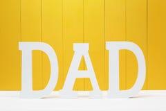 Lettres des textes de PAPA sur le fond en bois jaune Photo libre de droits