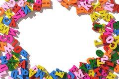 Lettres en bois colorées présentées autour sur une table blanche la disposition de l'isolat Image libre de droits