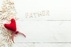 Lettres en bois dispersées et un coeur rouge Images stock