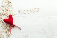 Lettres en bois dispersées et un coeur rouge Photographie stock libre de droits