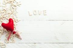Lettres en bois dispersées et un coeur rouge Images libres de droits