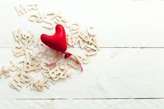 Lettres en bois dispersées et un coeur rouge Photographie stock