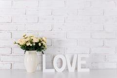 Lettres en bois formant le mot AMOUR et fleurs au-dessus du wa blanc de brique Images stock