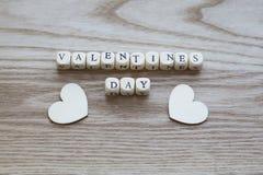 Lettres en bois orthographiant le jour de valentines sur un fond en bois avec le coeur deux en bois placé ci-dessous Photographie stock