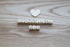 Lettres en bois orthographiant le jour de valentines sur un fond en bois avec un coeur en bois placé ci-dessus Photo libre de droits