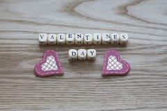 Lettres en bois orthographiant le jour de valentines sur un fond en bois avec des deux coeurs piqués rouges et crèmes mignons ci- Photos libres de droits