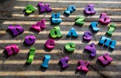 Lettres en plastique colorées d'alphabet sur un fond en bois Image libre de droits