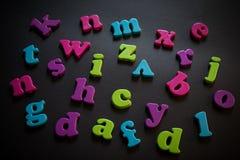 Lettres en plastique colorées d'alphabet sur un fond noir Photographie stock libre de droits