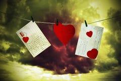 Lettres et coeur de carton accrochant par un fil Images stock