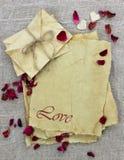 Lettres et enveloppes d'amour antiques de papier parcheminé avec les pétales de rose rouges Photos stock
