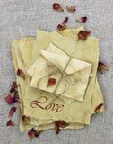 Lettres et enveloppes d'amour faites de papier parcheminé antique avec les pétales de rose secs Photo stock