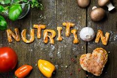 Lettres et légumes de la pâte sur la table en bois rustique, nutrit de mot Image stock