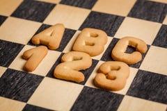 Lettres et nombres de biscuit sur un vieux checkboard photographie stock