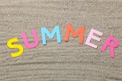 Lettres multicolores de papier d'été d'inscription sur le sable de mer ?t? Relaxation Vacances Vue sup?rieure images stock