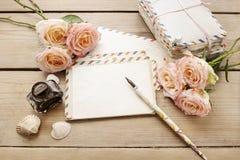 Lettres, roses et bouteille de vintage d'encre sur la table en bois Photographie stock libre de droits