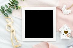 Lettreting mock up template white border photo frame with black background, mini house and Human model dummy. Flat lay. Lettreting mock up template white photo Royalty Free Stock Photography