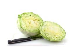 Lettuce. A head of iceberg lettuce, cut in half, with knife Stock Photos