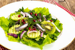 Lettuce with anchovies and pomegranate seeds Stock Photos