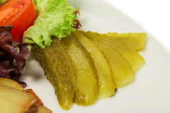 Lettuce closeup with marinated cucumbers. Stock Images