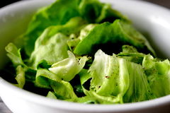 Lettuce with dressing. And freshly ground, black pepper in a white salad bowl stock images
