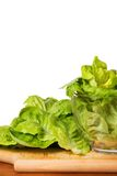Lettuce in glass bowl on a wooden plate Royalty Free Stock Photo