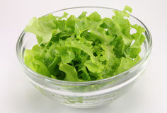Lettuce in a glass salad bowl transparent. Lettuce in a glass transparent salad bowl on a white background Royalty Free Stock Images