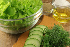 Lettuce in a glass transparent salad bowl with spices. On a wooden background Stock Photos