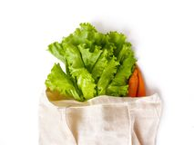 fresh lettuce leaves and carrots in a linen bag for shopping stock photography