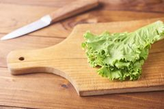 Lettuce leaves on cutting board with knife on wooden background. stock images