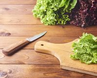 Lettuce leaves on cutting board with knife on wooden background. royalty free stock image