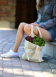 Lettuce. Linen bag full of fresh salad stands near the legs of stylish woman Royalty Free Stock Photos