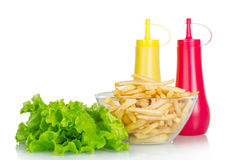Lettuce, mustard, ketchup with fries isolated on Royalty Free Stock Images