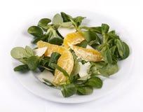 Lettuce, orange and feta cheese. Fresh lettuce on a plate, orange and feta cheese on a white background Stock Photography