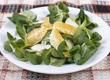 Lettuce, orange and feta cheese. Fresh lettuce on a plate, orange and feta cheese Stock Photo