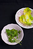 Lettuce and parsley leaves. In pink bowls on black background Stock Photo