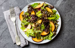 Lettuce salad with plums, slate background. Lettuce salad with plums, slate grey background. Top view Royalty Free Stock Images