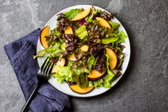 Lettuce salad with plums, slate background. Lettuce salad with plums, slate grey background. Top view Stock Photo