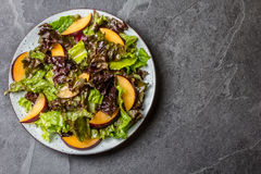 Lettuce salad with plums, slate background. Lettuce salad with plums, slate grey background. Top view Stock Photos
