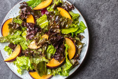 Lettuce salad with plums, slate background. Lettuce salad with plums, slate grey background. Top view Royalty Free Stock Photography