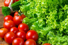 Lettuce salad, tomatoes and chives on wooden background. Stock Image