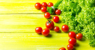 Lettuce salad, tomatoes and chives on wooden green background. Top view stock image