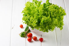 Lettuce salad, tomatoes and green onion on white background. Lettuce salad in wihte bowl, tomatoes and green onion on wooden white background stock images